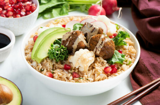 White bowl filled with fried rice, kale, deep fried falafel, avocado and pomegranate seeds topped with tahini sauce