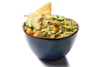 Bowl filled with avocado and mango rice dip with diced tomatoes, avocado chunks and crunchy tortilla chips