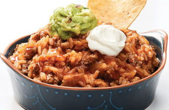 Hearty enchilada dip with jasmine rice, guacamole, sour cream and tortilla chips