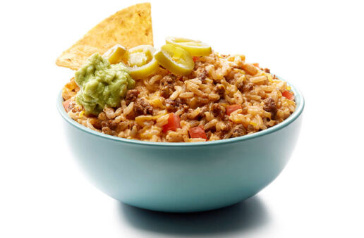Bowl with loaded nacho jasmine rice dip with jalapeños, guacamole and tortilla chips