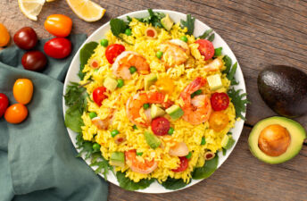 White bowl with paella salad, diced avocados, cherry tomatoes, shrimp, chicken and olives