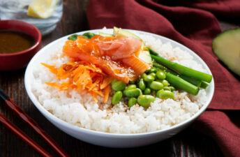 Poke bowl with sushi rice, salmon, asparagus, avocado, miso, edamame, sesame and orange