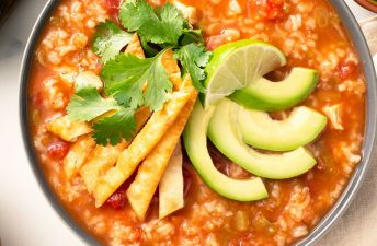 Chicken tortilla rice soup with avocado and lime