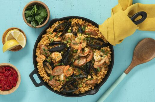 Traditional-Paella-Dish-with-Red-Bell-Peppers-Lime-Wedges-Chorizo-Shrimp-Mussels-and-Fresh-Parsley