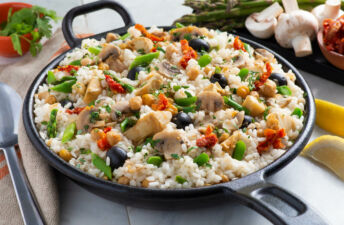 Skillet with vegetarian paella, black olives, mushrooms and