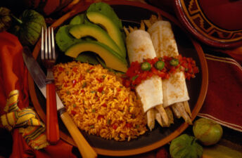Spanish brown rice with avocado slices, tortillas and chicken