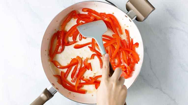 Sauteed red peppers in a pan